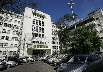 Fachada do Complexo HUPES - prédio antigo, com porta rande e acessível para cadeirantes, rodeado por árvores e carros no estacionamento